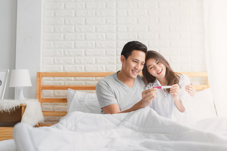 Photo pour Happy Asian couple smiling after find out positive pregnancy test in bedroom at home - image libre de droit