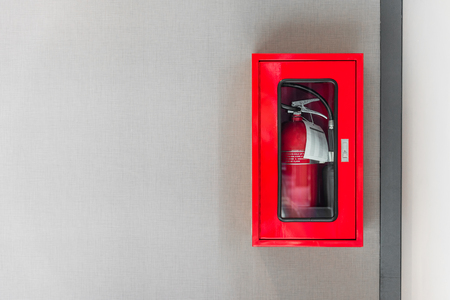 Foto de fire extinguishers cabinet on grey wall background in office building - Imagen libre de derechos