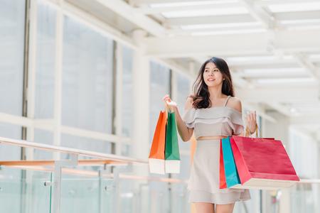 Foto de Portrait of happy young Asian woman with shopping bags walking in the mall - Imagen libre de derechos