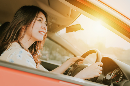 Photo for Confident and smile beautiful Asian woman driving a car in morning sunlight - Royalty Free Image