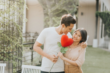 Photo pour Romantic happy Asian couple in love having fun with heart flower while hugging. Vanlentine day concept. - image libre de droit