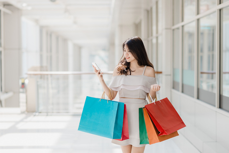 Photo for Beautiful young happy Asian woman with colorful shopping bag using smartphone while shopping in mall - Royalty Free Image