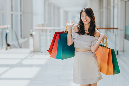 Photo for Happy Asian beautiful woman enjoying and smiling with colorful shopping bag in her both hand in mall.  - Royalty Free Image