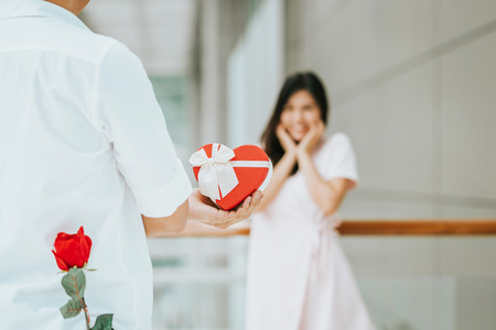 Foto de Rear view of a young man give present gift box with rose behind his back to his lovely girlfriend who look surprise - Imagen libre de derechos