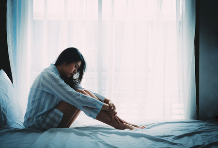 Photo pour Unhappy beautiful Asian woman sitting on a bed looking sad and lonely - image libre de droit