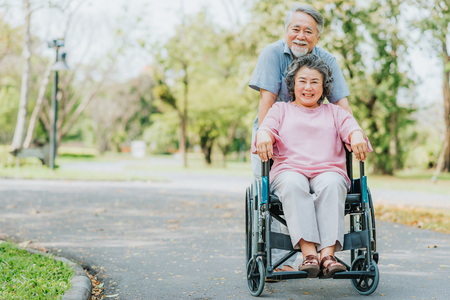 Foto de Happy smile Asian senior woman in a wheelchair relaxing and walking with her husband outside at the park - Imagen libre de derechos
