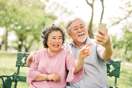 Foto de Happy senior Asian couple laughing and smiling together while looking at smartphone mobile - Imagen libre de derechos