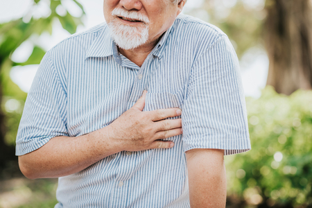 Photo for Cropped shot of senior man holding his chest and feeling pain suffering from heart attack outdoor at the park - Royalty Free Image