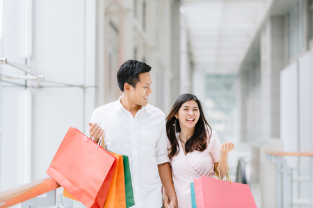 Photo pour Happy Asian couple holding colorful shopping bags and enjoying shopping, having fun together in mall. Consumerism, love, dating, lifestyle concept - image libre de droit
