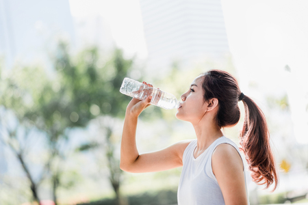 Photo for Shot of a young Asian woman drinking water from water bottle after jogging in the park. - Royalty Free Image
