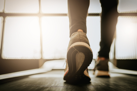 Foto per Close up shot of woman leg running in a gym on a treadmill for exercise. fitness and healthy lifestyle concept - Immagine Royalty Free