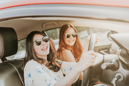 Photo pour Two happy Asian girl best friends laughing and smiling in car during a road trip to vacation. - image libre de droit