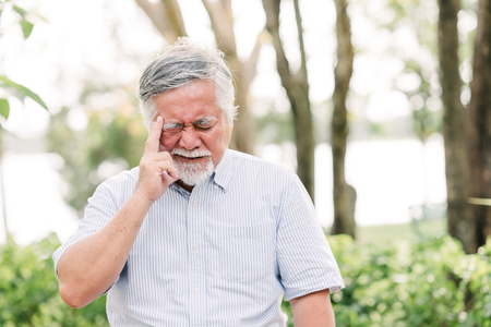 Photo for Portrait of Asian senior man sitting in the park suffering from a headache - Royalty Free Image