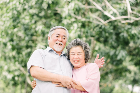 Photo for Happy Asian senior couple having a good time. They laughing and smiling while holding each other outdoor in the park. - Royalty Free Image