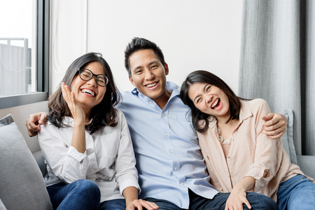 Foto de Group of happy three Asian best friends in casual wear laughing and smiling together in living room - Imagen libre de derechos