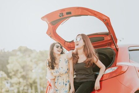 Photo for Two happy Asian girl best friends traveler laughing and smiling while sitting in red car trunk  - Royalty Free Image