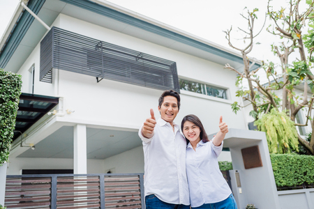 Foto de Happy Asian couple with thumb up standing together in front of thier house - Imagen libre de derechos