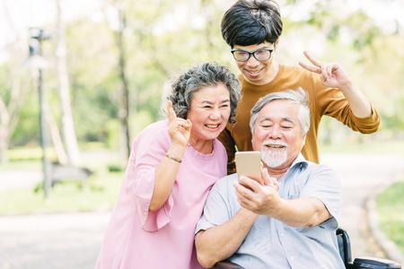 Foto de Happy Asian seniors family having fun with smartphone in the park - Imagen libre de derechos