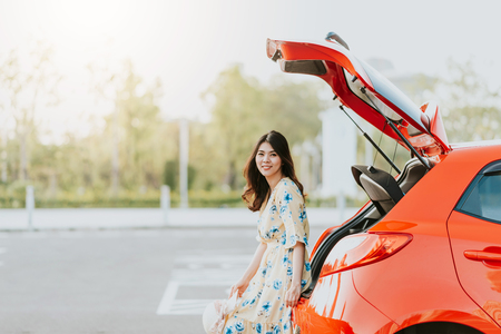 Photo for Happy Asian woman traveler sitting on car trunk during vacation - Royalty Free Image