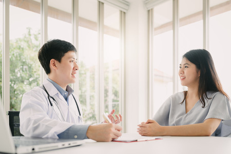 Photo pour Asian doctor having consultation with young female patient in office - image libre de droit