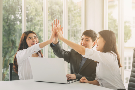 Foto de Gropu of young Asian business people giving high five to celebrate success on working project in meeting room - Imagen libre de derechos