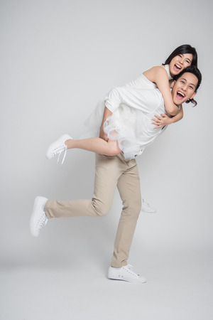 Foto de Happy Asian groom gives a bride piggyback ride on white background. - Imagen libre de derechos