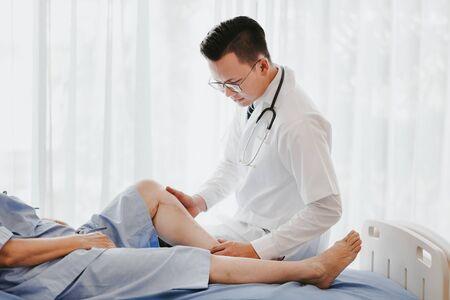 Foto de Shot of a traumatologist doctor examining his patient knee on the bed in hospital - Imagen libre de derechos
