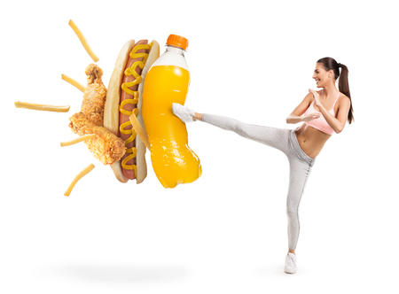 Photo pour Fit young woman fighting off soda and junk food - image libre de droit