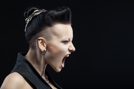 Foto de angry young woman screaming isolated on black background with copyspace - Imagen libre de derechos