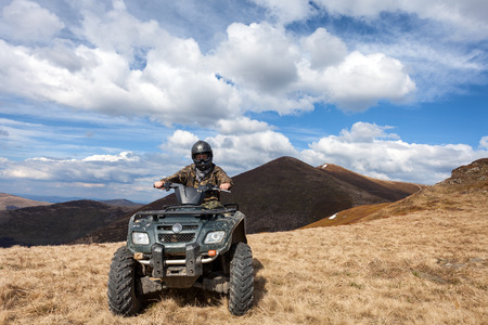 Photo pour male rider sitting on ATV at mountain top - image libre de droit