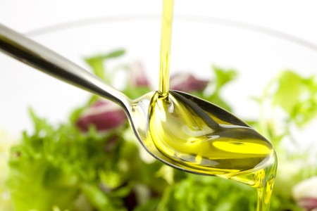 Pouring olive oil in the salad over a spoon
