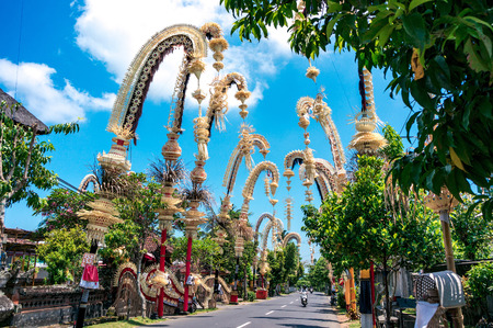 Photo for Traditional balinese penjors along the street of Bali, Indonesia. Tall bamboo poles with decoration are set in honour of hindu gods on religious festivals like Galungal, Kuningan. - Royalty Free Image