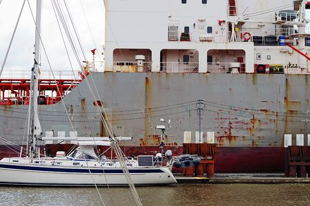 Foto per View of a sailboat in front of a freighter - Immagine Royalty Free