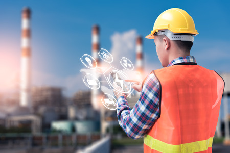 Photo pour The abstract image of the engineer holding smartphone with hologram and the blurred power plant is backdrop. the concept of clean energy, futuristic, industrial4.0 and internet of things. - image libre de droit