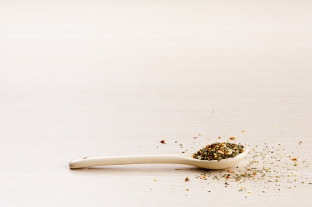 Italian Seasoning in a spoon with some spilt over the wooden background