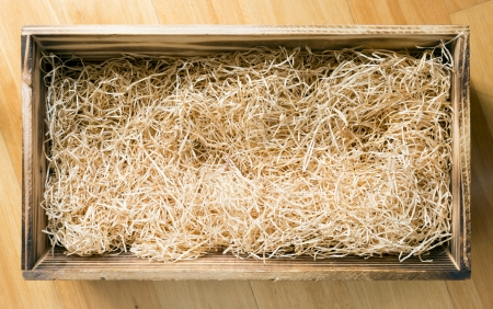 Foto de Wooden gift or display box filled with natural raffia or twine - Imagen libre de derechos