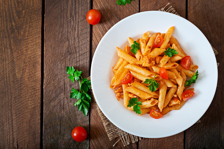 Photo pour Penne pasta in tomato sauce with chicken, tomatoes on a wooden background - image libre de droit