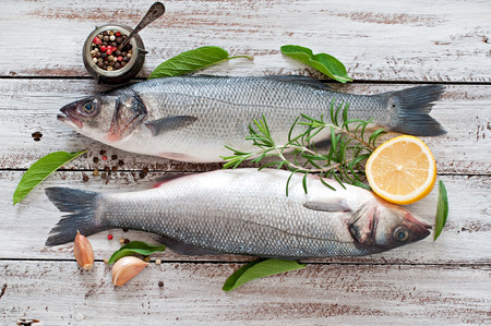 Foto de Two raw seabass with spices on an old wooden background. - Imagen libre de derechos