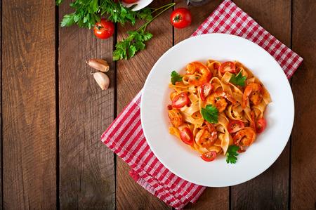 Photo pour Fettuccine pasta with shrimp tomatoes and herbs - image libre de droit
