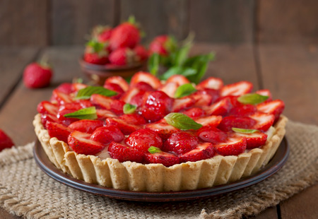 Foto de Tart with strawberries and whipped cream decorated with mint leaves - Imagen libre de derechos