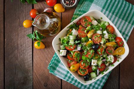 Foto de Greek salad with fresh vegetables, feta cheese and black olives - Imagen libre de derechos