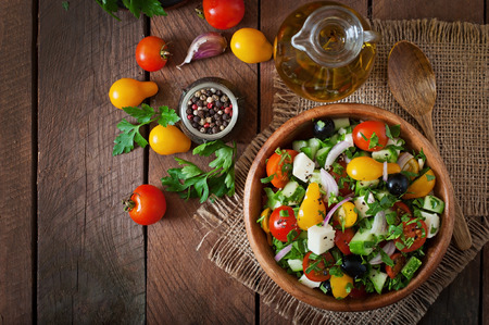 Foto de Greek salad with fresh vegetables, feta cheese and black olives - Imagen libre de derechos