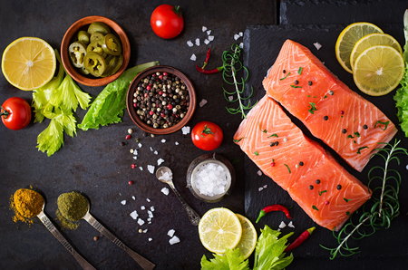 Photo pour Raw salmon fillet and ingredients for cooking on a dark background in a rustic style. Top view - image libre de droit