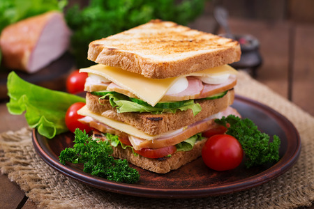 Photo for Club sandwich with cheese, cucumber, tomato, ham and eggs. - Royalty Free Image