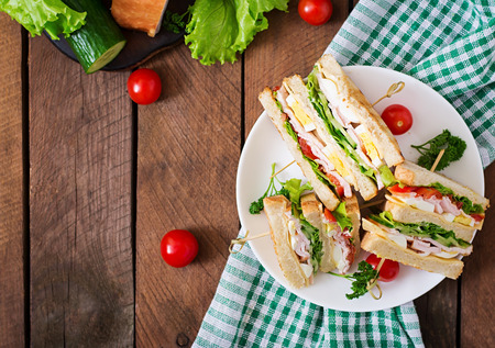Photo for Club sandwich with cheese, cucumber, tomato, ham and eggs. Top view - Royalty Free Image