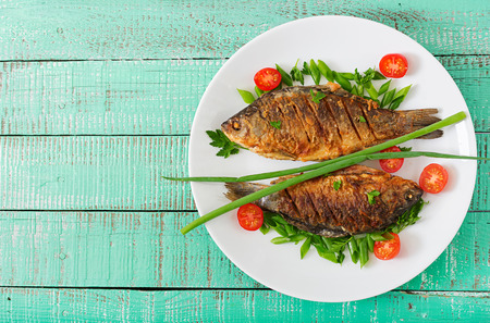 Foto de Fried fish carp and fresh vegetable salad on wooden background. Flat lay. Top view - Imagen libre de derechos