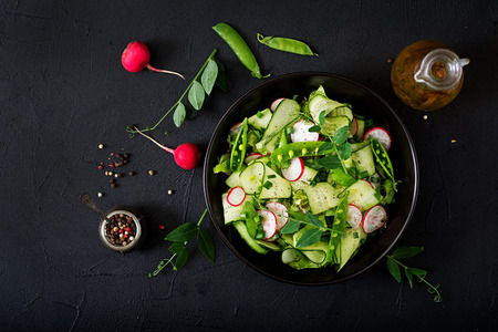Photo pour Fresh salad of cucumbers, radishes, green peas and herbs. Flat lay. Top view - image libre de droit