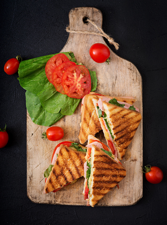 Photo for Club sandwich panini with ham, tomato, cheese and basil. Flat lay. Top view - Royalty Free Image