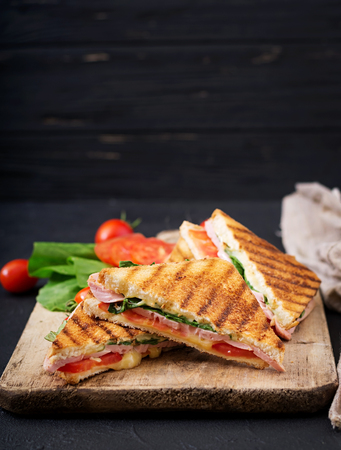Foto de Club sandwich panini with ham, tomato, cheese and basil. - Imagen libre de derechos