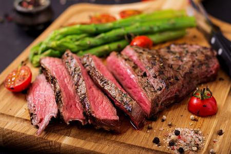 Photo pour Juicy steak rare beef with spices on a wooden board and garnish of asparagus. - image libre de droit